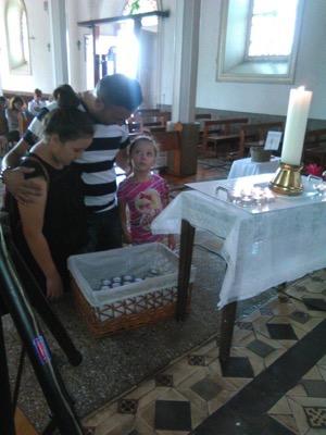 Papá con dos niñas encendiendo velas